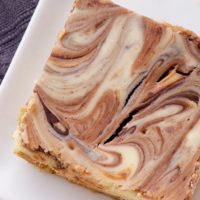 Nutella Swirl Cheesecake Bars feature a swirl of that favorite chocolate-hazelnut spread in sweet, rich cheesecake bars! - Bake or Break