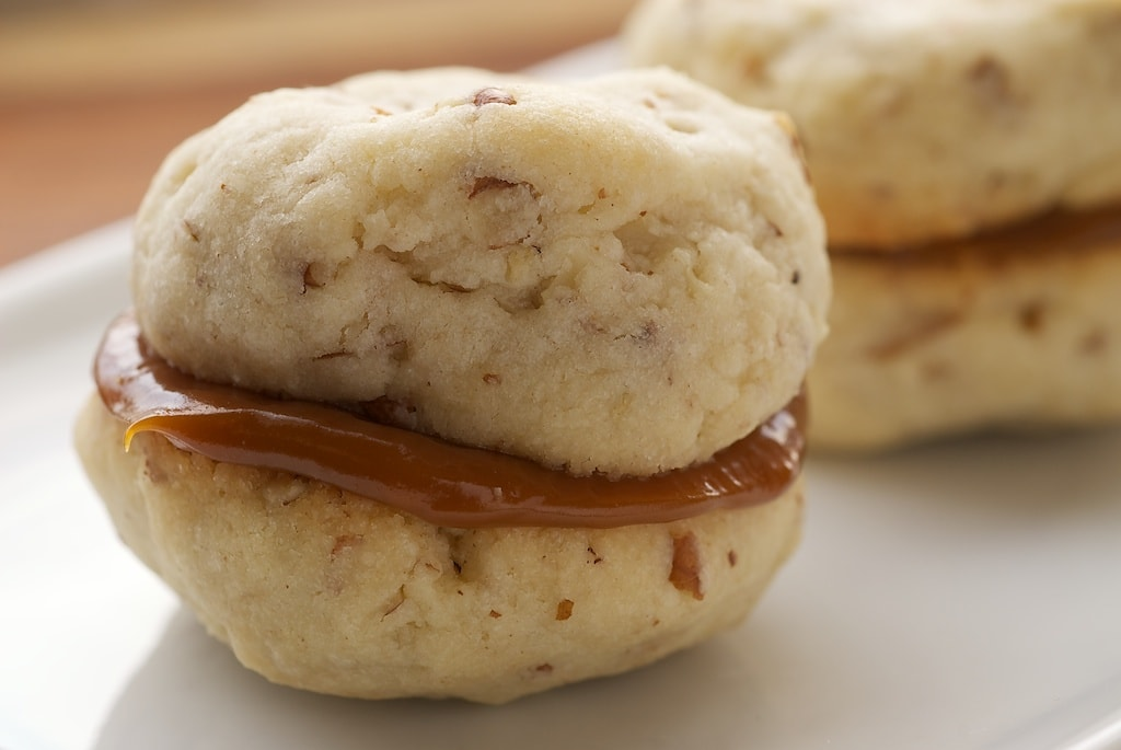 Cream Cheese Shortbread-Dulce de Leche Sandwich Cookies combine a soft, light, nutty shortbread with rich dulce de leche for an irresistible cookie. - Bake or Break