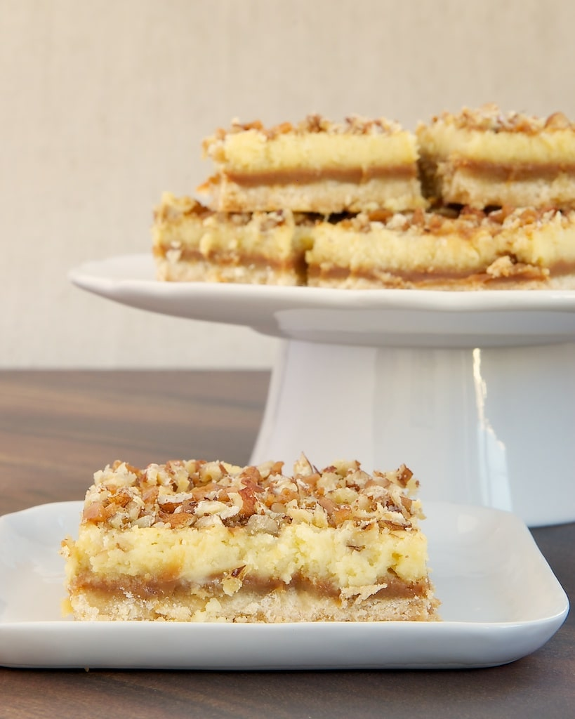 Caramel Cream Cheese Bars feature delicious layers of shortbread, caramel, cream cheese, and nuts. - Bake or Break