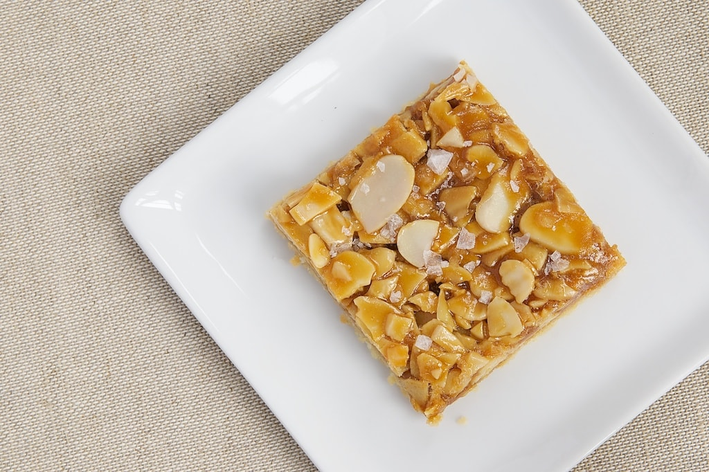 Salted Caramel Almond Bars start with a buttery crust, followed by caramel, almonds, and a sprinkling of salt. A sweet and salty favorite! - Bake or Break