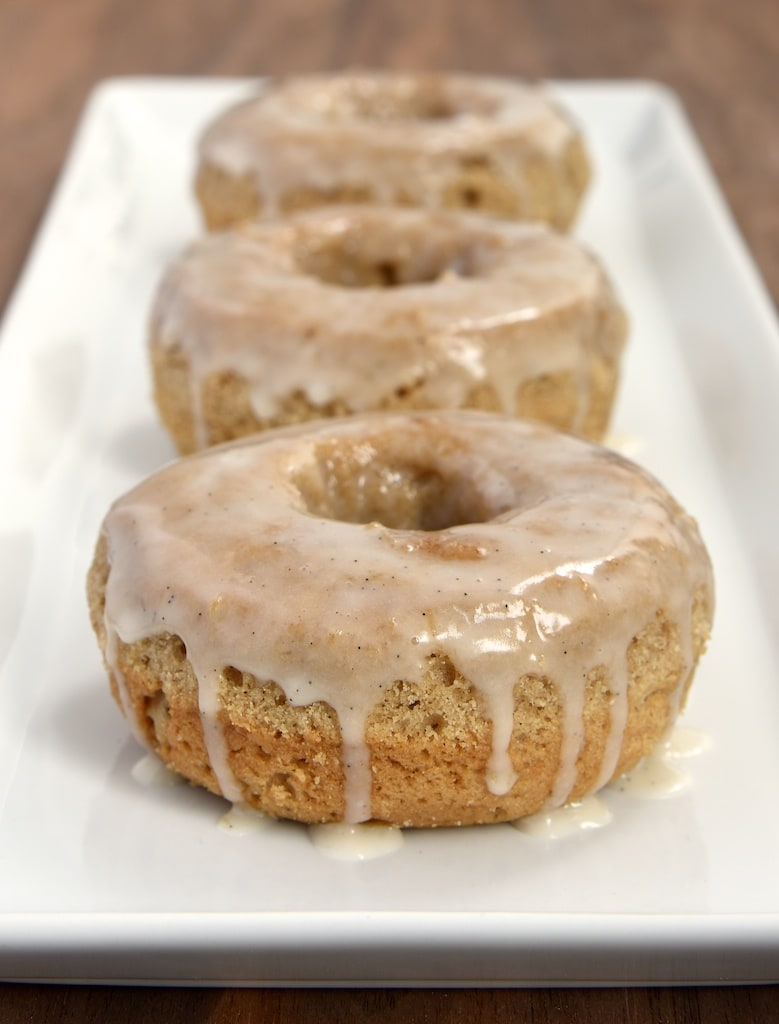These baked doughnuts are flavored with lots of delicious spices and topped with a sweet vanilla glaze.