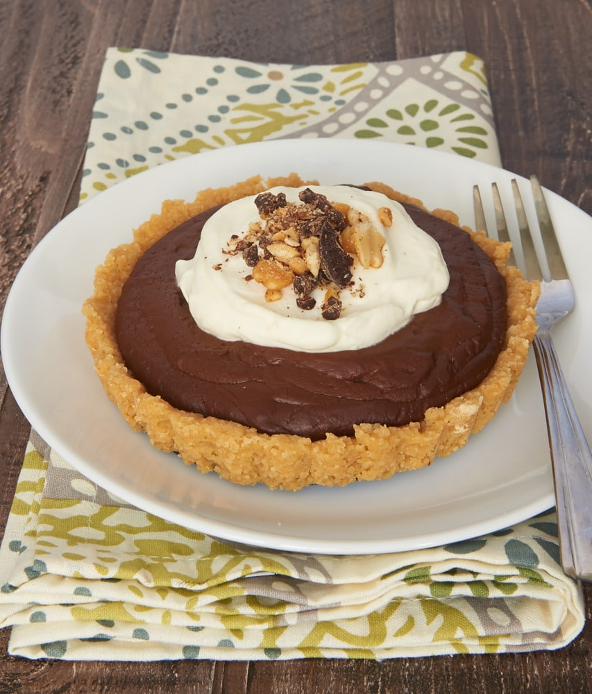 Rich pudding and a sweet shortbread crust make these Chocolate Peanut Butter Pudding Tarts absolutely irresistible! - Bake or Break