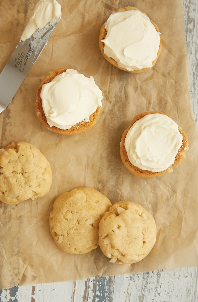 White Chocolate Macadamia Sandwich Cookies are a fun, frosted twist on a classic cookie. That white chocolate frosting is fantastic! - Bake or Break